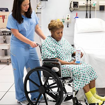 Nurse pushing a patient with an NPWT device and slippers in a wheelchair.