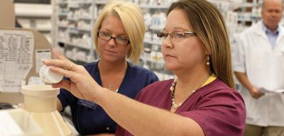 Pharmacy techs filling a prescription.