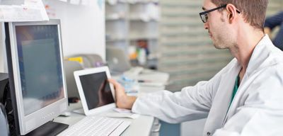 Physician looking at something on a tablet and computer monitor.