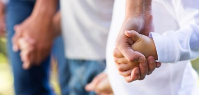 Close up of a group holding hands.