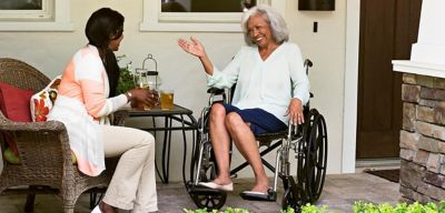 A woman in a wheelchair having tea with another woman on the front porch.