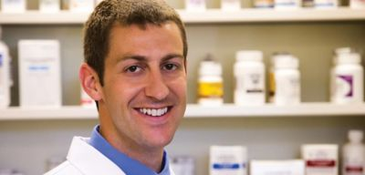 Smiling pharmacist wearing a blue shirt standing in front of the pharmacy shelves.